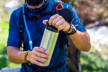 Hiker Opening Thermos On A Hik...