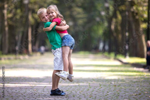 Obraz na plátně Two cute young funny smiling children, girl and boy, brother holding sister in his arms, having fun on blurred bright sunny park alley green trees bokeh background