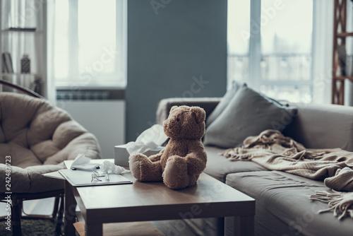 Fotografia  Teddy bear sitting on coffee table in living room