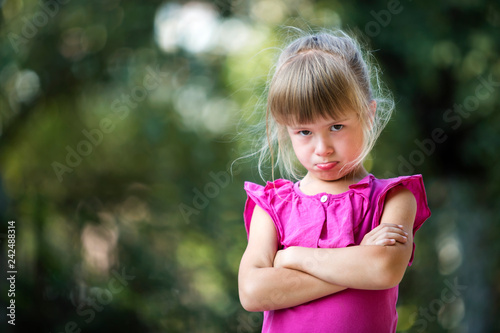 Fotografie, Obraz  Portrait of pretty funny moody unhappy young blond child girl in pink sleeveless dress feeling angry and unsatisfied on blurred summer green tree copy space bokeh background