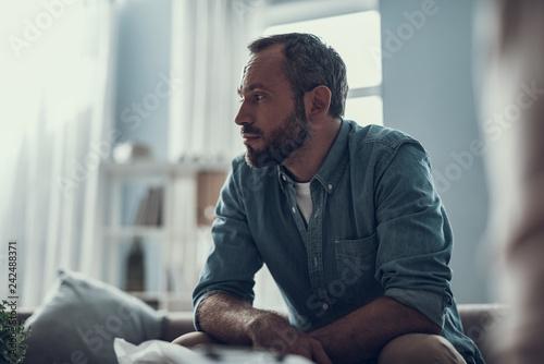 Fotografía Waist up of bearded man thoughtfully looking away
