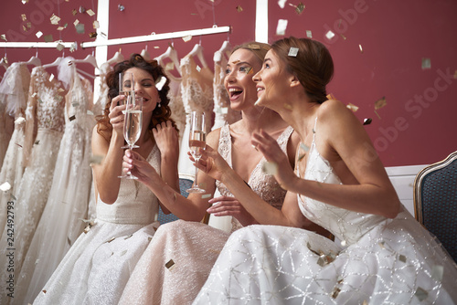 Fotografie, Obraz Waist up of cheerful brides with champagne glasses