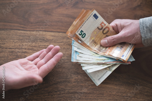Fotografía  hand of one person handing over cash to another