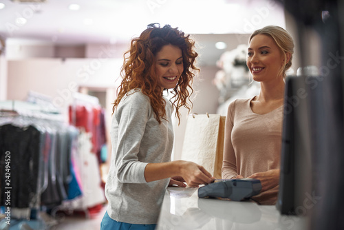 Young smiling lady making payments by credit card Fototapete