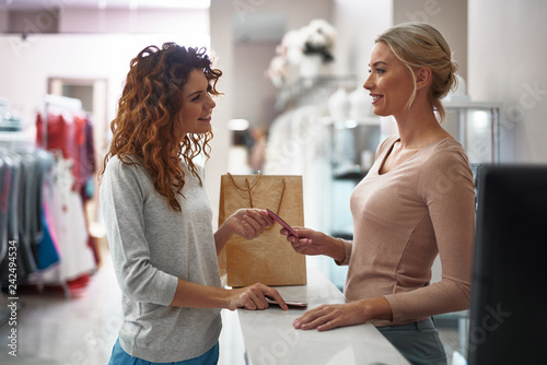 Leinwand Poster Young smiling lady giving credit card on register