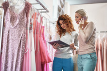 Two Beautiful Ladies Choosing Dress From Catalogue