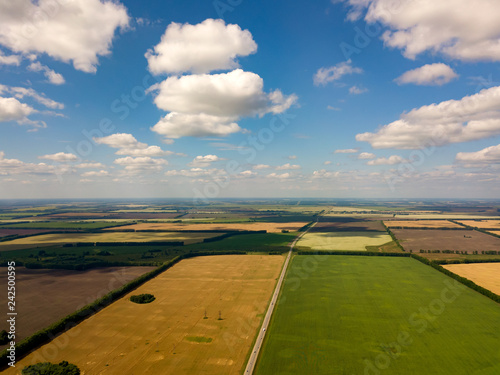Picturesque aerial view of farmland in the countryside, blue sky with white clouds, colorful fields with different planted crops, green grass and lake trees, rural expanses outside the city Fototapeta