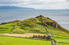 Torr Head Headland, Rocky Cliff And Peninsula With Ruins Of Old Fort In County Antrim, Northern Ireland, Near Ballycastle. Far View Of Rathlin Island And Scotland In The Background