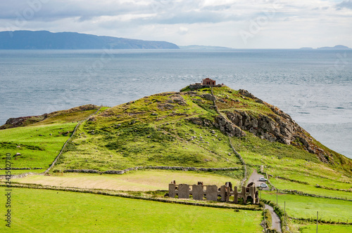 Fotografie, Obraz  Torr Head headland, rocky cliff and peninsula with ruins of old fort in County Antrim, Northern Ireland, near Ballycastle