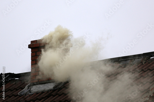 Smoke from the chimney of a house fueled with coal. Fotobehang