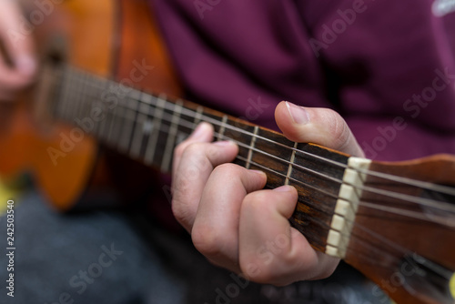 Fotografía  Young unidentifiable musician playing on the guitar shallow depth of field