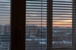 Window with blinds silhouette in morning or evening twilight, urban landcsape on background