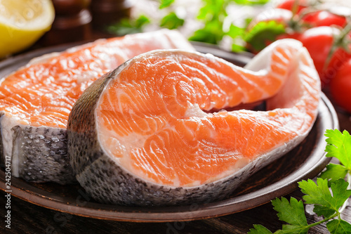 Cooking two fresh raw salmon fish steaks on wooden rustic table closeup