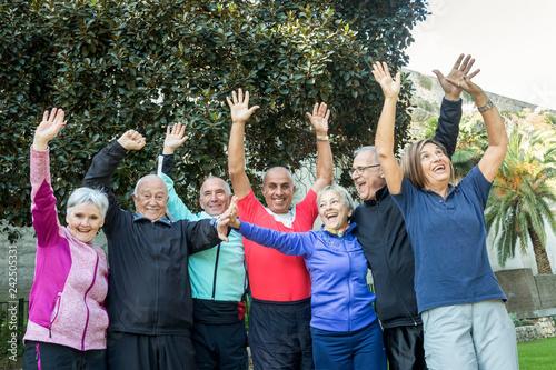 Gruppo di anziani felici che sollevano le braccia al cielo e ridono Wallpaper Mural