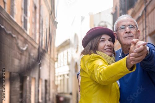 Fotografia  Coppia matura in vacanza accenna un ballo per le vie della città