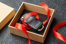 Gift Box With Car Keys With Remote Control Alarm System With Red Ribbon Bow.
