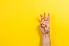Man Hand Showing Three Fingers On Yellow Background. Number Two Symbol