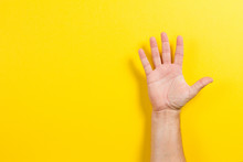 Man Hand Showing Five Fingers On Yellow Background. Number Two Symbol