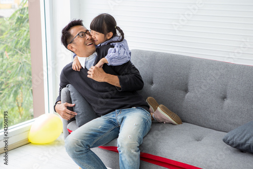 9c92df185 happy family Cute little girl daughter and father are hugging and playing  on sofa in living
