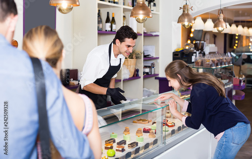 Fototapeta Confectioner helping customers to choose sweets