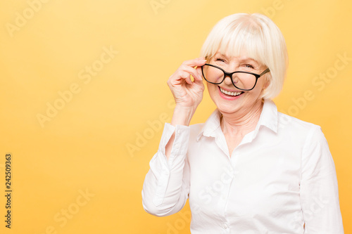 Joyful senior lady in glasses laughing isolated over yellow background Poster Mural XXL