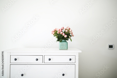 The bunch of little pink roses on the chest of white drawers in the white interi Wallpaper Mural