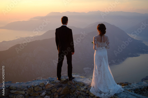 Photo  back of the bride and groom standing on top of the mountain at sunset