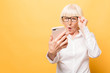 Leinwanddruck Bild - Wow! Phone conversation. Surprised aged woman using phone, isolated over yellow background.