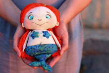 Textile Handmade Doll Of Little Mermaid In The Hands Of A Woman. Little Doll With Orange Hair And Fish Tail.