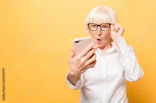 Wow! Phone conversation. Surprised aged woman using phone, isolated over yellow background.