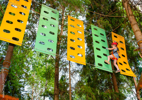 Little girl on a ropes course in a treetop adventure park passing hanging rope o Fototapet
