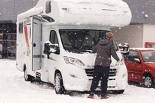 Camping Car Or Campervan Getting Ready In The Parking Space And Man Clean It For Outdoor Journey On The Mountain Side In The Snow