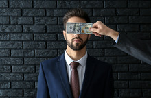 Man With Bribe Covering Eyes Of Businessman Against Dark Brick Background. Concept Of Corruption