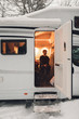camping car or campervan outdoor on the mountain side offroad near the forest in the winter snowing