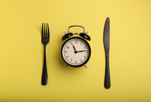 Alarm Clock And Cutlery On Col...