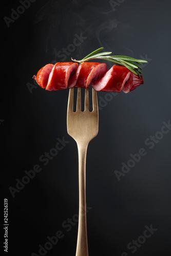 Obraz na płótnie Grilled sausage with rosemary on a fork.