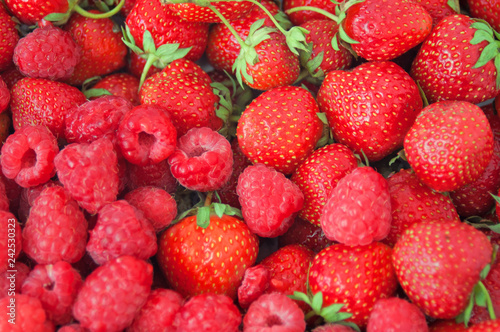 fresh raspberries and strawberries background closeup