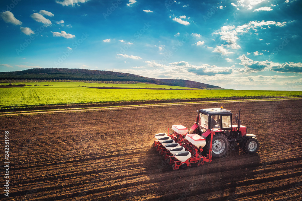Fototapeta Farmer with tractor seeding crops at field, aerial drone view