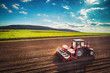 Leinwanddruck Bild - Farmer with tractor seeding crops at field, aerial drone view