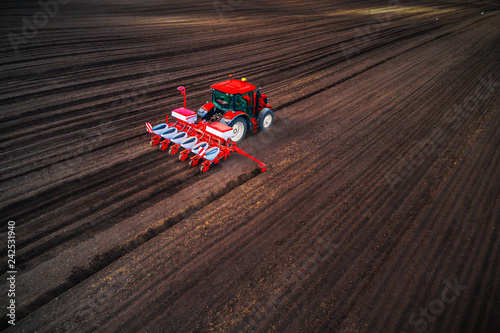 Photo  Farmer with tractor seeding crops at field, aerial drone view