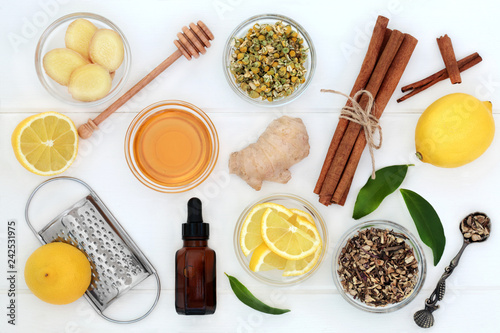 Ingredients for cold and flu remedy with ginger and cinnamon spice, eucalyptus aromatherapy oil, lemon fruit with honey on white wood background Canvas Print