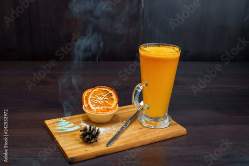 Foto op Plexiglas Cocktail Hot spicy tea drink of yellow color with jam with slices of dried orange stands on the table against a dark background. The drink is decorated with fir cone. Cozy atmosphere.