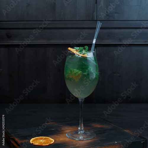 Foto op Plexiglas Cocktail Pineapple light alcoholic mojito cocktail in an elegant glass of vodka with white rum with coconut syrup with pieces of ice decorated with yellow fruit is in the bar. Selection of modern gourmet.