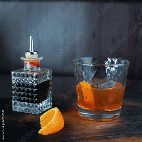 Foto op Plexiglas Cocktail Alcoholic sweet fruit syrup with a slice of orange stands on a wooden table in a bar next to a crystal bottle with a brown drink. Weekend in a nightclub