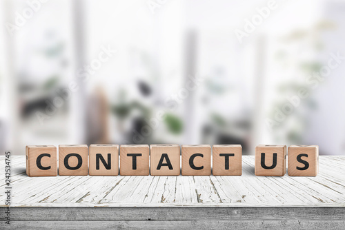 Photo  Contact us sign on a wooden desk
