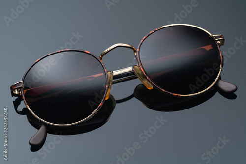 Foto  sunglasses with round frame on dark background