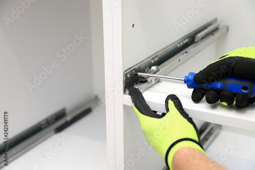 Fotografie, Tablou  Robotnik wkręca śrubę w prowadnicy mebli.