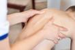 Badanie wady postawy u dziecka. Dłonie lekarza badają kręgosłup małego pacjenta.