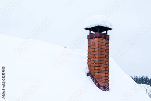 Tablou Canvas Red brick chimney with iron chimney cap on the roof in snow.