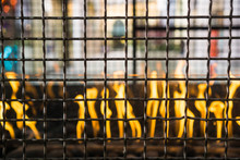 Metal Grid Enclosing An Outdoors Fire Used For Getting Warm In An Open Air Shopping Center